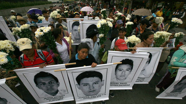 Mothers and relatives of the 43 missing students from the Isidro Burgos rural teachers college, with posters with the images of their missing loved ones walk in to attend a mass at the Basilica of Guadalupe in Mexico City on Oct. 19, 2014. Investigators determined that 28 sets of human remains recovered from a mass grave discovered last weekend outside Iguala, in Guerrero state, were not those of any of the youths who haven't been seen since being confronted by police in that city Sept. 26. (AP Photo/Marco Ugarte)