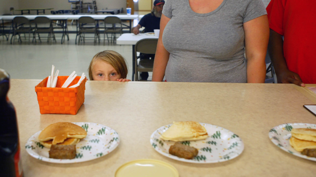 Emma Robertson, 3, peers above the counter as she waits in line Tuesday, Aug. 12, 2014, for pancakes and sausage at the Spirit of Faith soup kitchen in Jacksonville, Ill. (AP Photo/Jacksonville Journal Courier, Bre Linstromberg Copper)