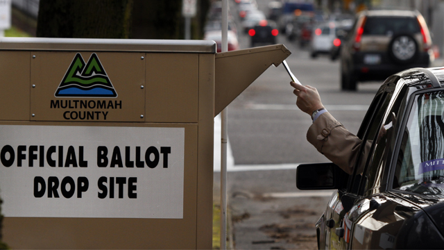 FILE - In this Jan. 30, 2012 file photo, a motorist drops of a ballot for the special election for Oregon's first congressional district in Portland, Ore. Oregon voters will decide this fall whether to adopt the top-two election system used in Washington and California. The measure would eliminate the current system of selecting party nominees. All voters, regardless of party, could vote in the May primary, with top two vote-getters advancing to the general election in November.(AP Photo/Don Ryan, file)