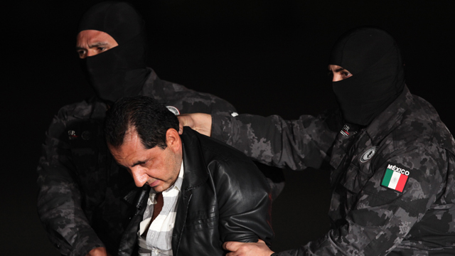 """Flavio Gomez, identified by police as the brother of Servando """"La Tuta"""" Gomez, the head of the Knights Templar drug cartel, is escorted to a federal police truck at the airport in Mexico City on Feb. 27, 2015. Servando Gomez, a former school teacher who became one of Mexico's most-wanted drug lords, was captured early Friday by federal police in Morelia, the capital of the western state of Michoacan.(AP Photo/Marco Ugarte)"""
