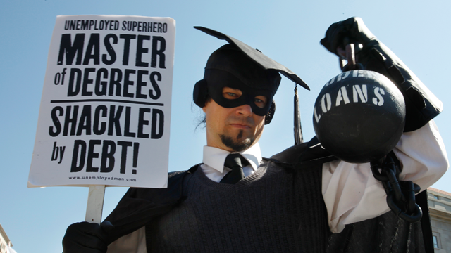 """In this Oct. 6, 2011 photo, Gan Golan, of Los Angeles, dressed as the """"Master of Degrees,"""" holds a ball and chain representing his college loan debt, during Occupy DC activities in Washington. As President Obama prepared to announce new measures Wednesday to help ease the burden of student loan debt, new figures painted a demoralizing picture of college costs for students and parents: Average in-state tuition and fees at four-year public colleges rose an additional $631 this fall, or 8.3 percent, compared with a year ago. (AP Photo/Jacquelyn Martin)"""