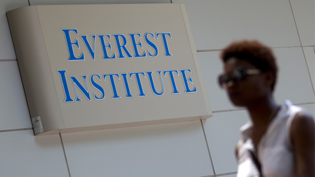 This photo taken July 8, 2014 shows a person walking past an Everest Institute sign in a office building in Silver Spring, Md. The Education Department says a former federal prosecutor will monitor a troubled for-profit education company that has agreed to sell or close its campuses. Corinthian Colleges has agreed to close a dozen U.S. campuses in 11 states and place 85 up for sale. The company serves 72,000 students and owns Everest College, Heald College and WyoTech schools. The department has said the company failed to provide adequate paperwork and comply with requests to address concerns about its practices. (AP Photo/Jose Luis Magana)