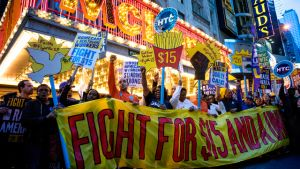 Protestors pause near a McDonald's restaurant in Times Square during a rally and march in New York, Wednesday, April 15, 2015, as participants, fast food workers and union members, call for a $15 minimum wage. (AP Photo/Craig Ruttle)