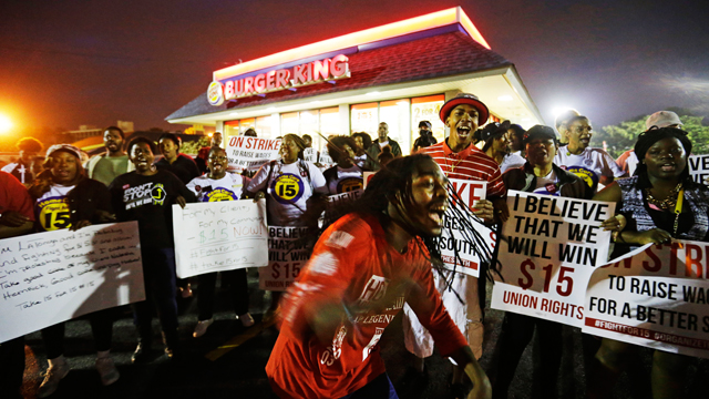 Joshua Collins, center, chants during a protest outside a Burger King restaurant by fast-food workers and activists calling for the federal minimum wage to be raised to $15 on April 15, 2015, in College Park, Georgia. Organizers say they chose April 15, tax day, to demonstrate because they want the public to know that many low-wage workers must rely on public assistance to make ends meet. (AP Photo/David Goldman)