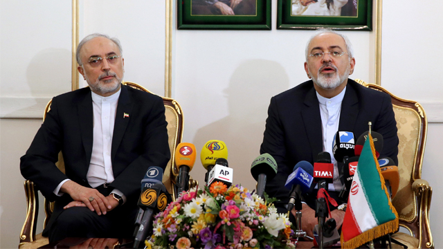 Iranian Foreign Minister Mohammad Javad Zarif, right, who is also Iran's top nuclear negotiator, speaks with media, as head of Iran's Atomic Energy Organization Ali Akbar Salehi listens, upon their arrival at the Mehrabad airport in Tehran, Iran, from Lausanne, Switzerland, Friday, April 3, 2015. Iran and six world powers reached a preliminary nuclear agreement Thursday outlining commitments by both sides as they work for a comprehensive deal aiming at curbing nuclear activities Tehran could use to make weapons and providing sanctions relief for Iran. Portraits of the Iranian late revolutionary founder Ayatollah Khomeini, left, and Supreme Leader Ayatollah Ali Khamenei, hang on the wall. (AP Photo/Ebrahim Noroozi)