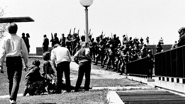 A group of youths cluster around a wounded person as Ohio National Guardsmen, wearing gas masks, hold their weapons in background on Kent State University campus in Kent, Ohio, Monday, May 4, 1970. Members of the Guards killed four students and injured nine during a campus protest against the Vietnam War. This picture was made by Kent State student photographer Douglas Moore. (Photo by Douglas Moore/AP)