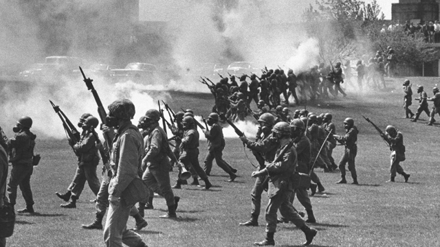 """FILE - In a May 4, 1970 file photo, Ohio National Guard moves in on rioting students at Kent State University in Kent, Ohio. Four persons were killed and eleven wounded when National Guardsmen opened fire. The US Justice Department, citing """"insurmountable legal and evidentiary barriers,"""" won't reopen its investigation into the deadly 1970 shootings by Ohio National Guardsmen during a Vietnam War protest at Kent State University. Assistant Attorney General Thomas Perez discussed the obstacles in a letter to Alan Canfora, a wounded student who requested that the investigation be reopened. The Justice Department said Tuesday, April 24, 2012 it would not comment beyond the letter. (AP File Photo)"""