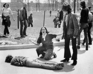 Mary Ann Vecchio gestures and screams as she kneels by the body of a student, Jeffrey Miller, lying face down on the campus of Kent State University, in Kent, Ohio. On publication, the image was retouched to remove the fencepost above Vecchio's head.