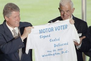 Bill Clinton holds up a t-shirt celebrating the 'Motor Voter Bill' passage and signing