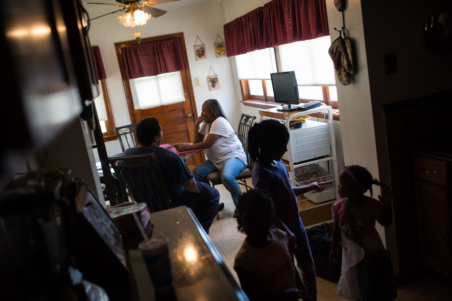 Sylvester and Gladys Clayborn sit in their kitchen as their granddaughters and great niece play nearby. The couple fell into debt when Gladys was permanently disabled after heart surgery. (Edwin Torres/ProPublica)