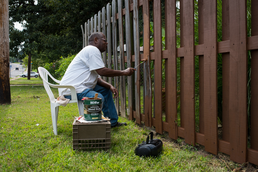Everett, a resident of Jennings, paints the fence of his home. (Edwin Torres/ProPublica)