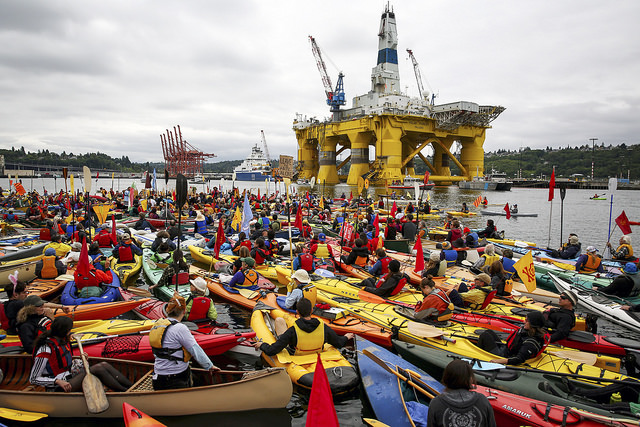 """Activists who oppose Royal Dutch Shell's plans to drill for oil in the Arctic Ocean prepare their kayaks for the """"Paddle in Seattle"""" protest on Saturday, May 16, 2015, in Seattle. The protesters gathered at a West Seattle park and then joined hundreds of others in Elliott Bay, next to the Port of Seattle Terminal 5, where Shell's Polar Pioneer drilling rig is docked. (Backbone Campaing / CC 2.0)"""