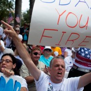 From left, Fatima Berrahal and Educardo Burkhart, of West Palm Beach, listen to billionaire Donald Trump as he addresses a crowd at the 2011 Palm Beach County Tax Day Tea Party on April 16, 2011 at Sanborn Square in Boca Raton, Florida. (Photo by John W. Adkisson/Getty Images)