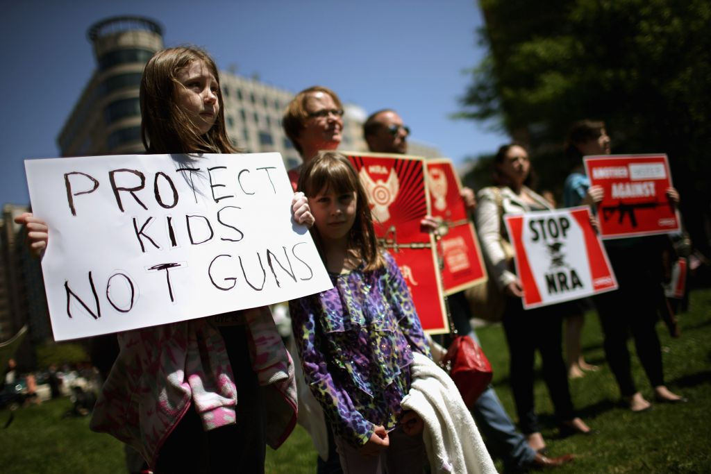 Anti-gun violence demonstrators, including Rachel Ahrens (L), 13, Abby Ahrens, 8, and their mother Betty Ahrens hold signs condemning the National Rifle Association during a protest in McPhearson Square April 25, 2013 in Washington, DC. (Photo by Chip Somodevilla/Getty Images)