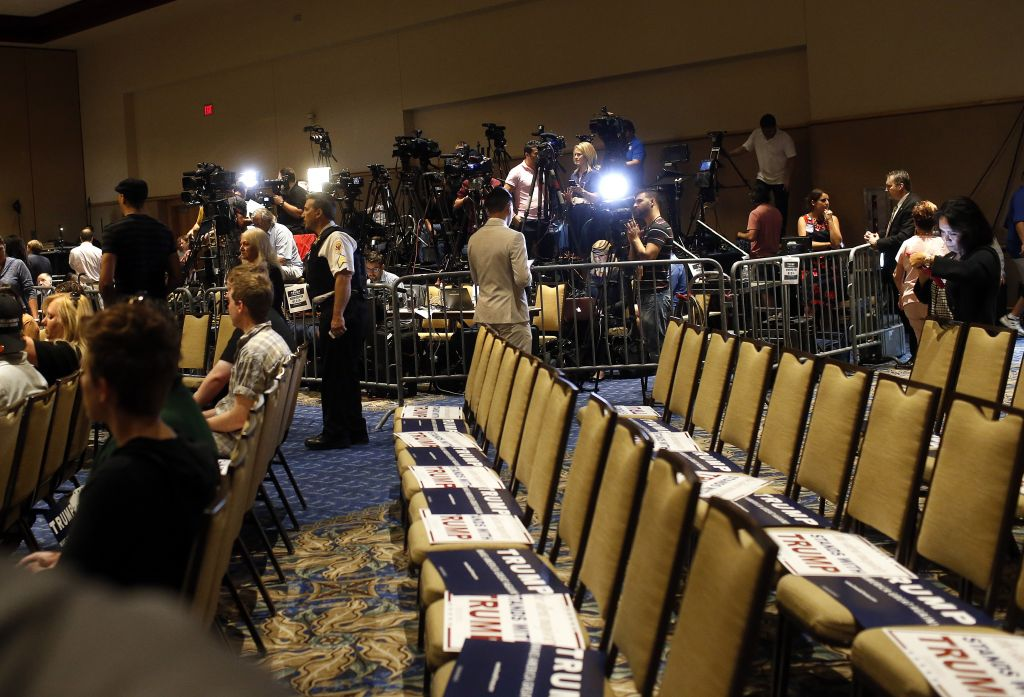 Caption: Members of the media work inside the designated media pen as they wait for Republican presidential candidate Donald Trump to arrive at a town hall meeting on March 14, 2016 at the Tampa Convention Center in Tampa , Florida. Members of the media were permitted to exit the pen and speak to attendees up until 30 minutes prior to the event start time. Trump is campaigning ahead of the Florida primary on March 15. (Photo by Brian Blanco/Getty Images)