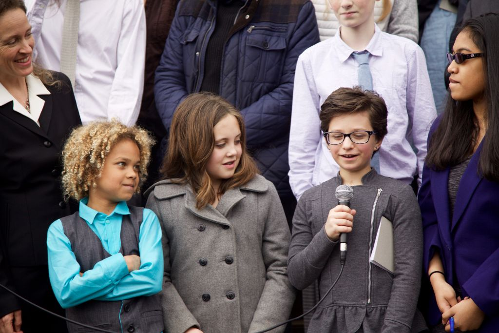 Levi Draheim (left, 8), Avery McRae (10) and Hazel Van Ummerson (11) respond to questions at a press conference after their hearing in Eugene, OR. (Clayton Aldern/Grist)