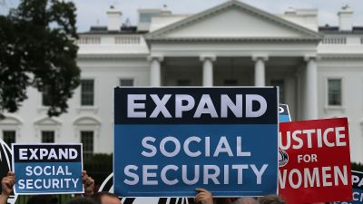 """Activists rally in front of the White House to urge the expansion of Social Security benefits July 13, 2015 in Washington, DC. Social Security Works, the AFL-CIO and additional organizations held the event to deliver """"more than 2 million petition signatures"""" in support of expanding benefits. (Photo by Win McNamee/Getty Images)"""