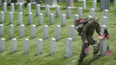 Soldier placing flags on gravesites at Arlington National Cemetery