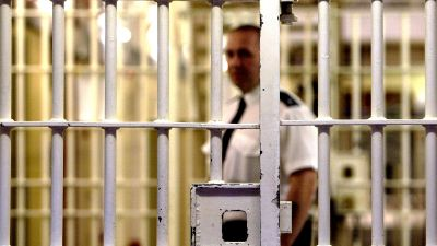 Prison guard seen through bars