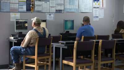 Dennis Evans (left) uses a computer at the public library in Decaturville, TN, a city that has never fully recovered from the closing of a clothing factory more than 20 years ago. Jobs are scarce and unemployment is high. (Photo by Bonnie Jo Mount/The Washington Post via Getty Images)