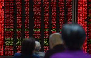 Investors watch price movements on screens at a securities company in Beijing on February 22, 2016. (GREG BAKER/AFP/Getty Images)