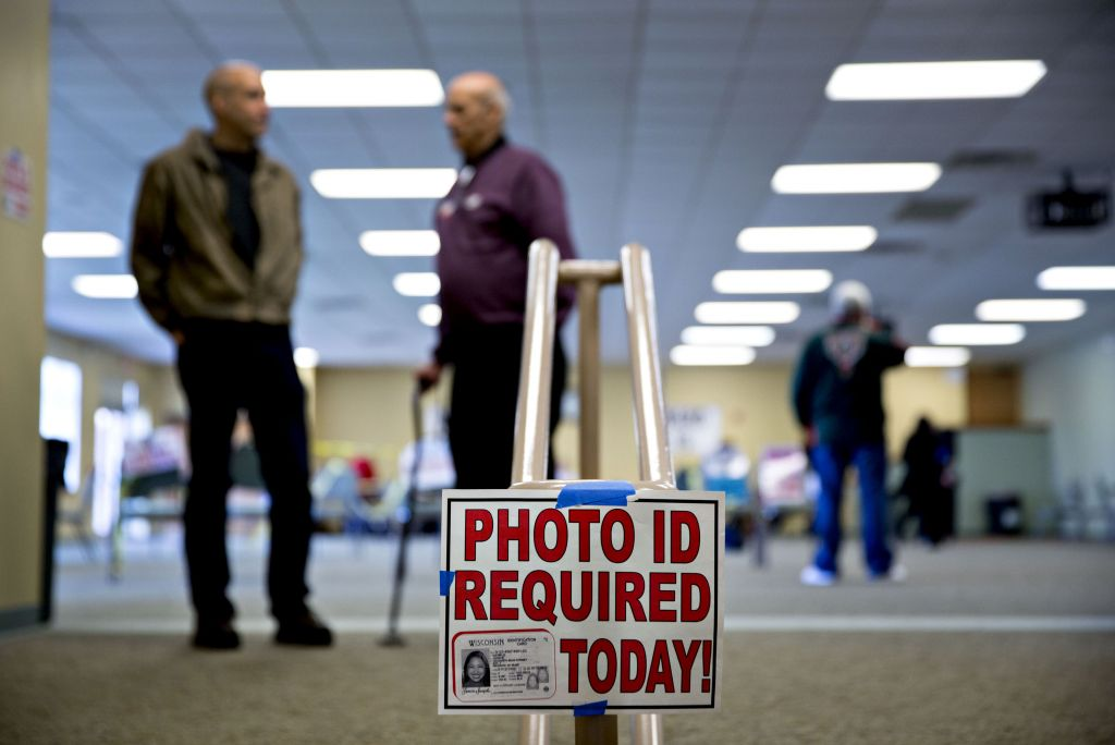"""A """"Photo ID Required Today"""" sign hangs at the entrance of a polling location in Waukesha, Wisconsin, during the 2016 primary. (Photographer: Daniel Acker/Bloomberg via Getty Images)"""