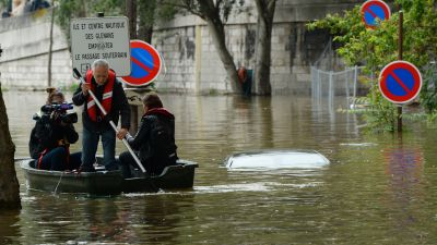 Journalists on a small boat pass near an immerged car in a flooded street along the quai Louis Bleriot in the 16th arrondissement in Paris on June 3, 2016 after the river Seine burst its banks. The rain-swollen river Seine in Paris reached its highest level in three decades. (Photo by Bertrand Guay/AFP/Getty Images)