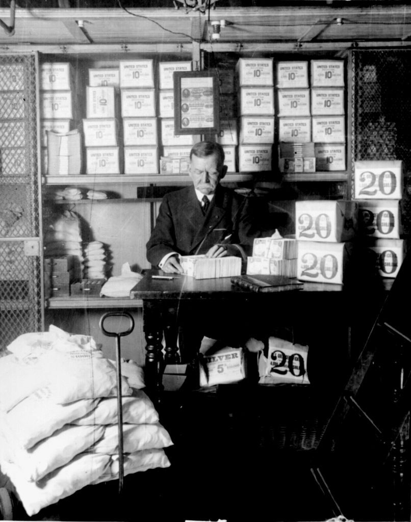 n US Treasury Department official, surrounded by packages of newly printed currency, counting and wrapping dollar bills in 1907. (National Archives via <a href='https://commons.wikimedia.org/wiki/File:Treasury_department_official_1907.jpg' target='blank'>Wikimedia Commons</a>)