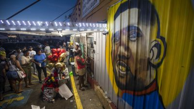 Protesters gather in front of a mural painted on the wall of the convenience store where Alton Sterling was shot and killed in Baton Rouge, Louisiana. Sterling was shot by a police officer in front of the Triple S Food Mart on Tuesday, July 5, leading the Department of Justice to open a civil rights investigation. (Photo by Mark Wallheiser/Getty Images)