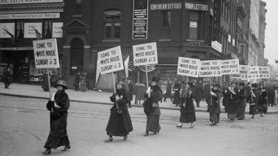 """A line of suffragists march with banners that read """"Come to the White House Sunday at 3,"""" in Washington DC in 1915. (Photo by Harris & Ewing/Buyenlarge/Getty Images)"""