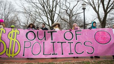 """Code Pink activists hold banner reading: """"$$$ out of politics."""""""