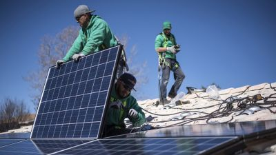 Workers installing solar panels to a New Mexico rooftop.