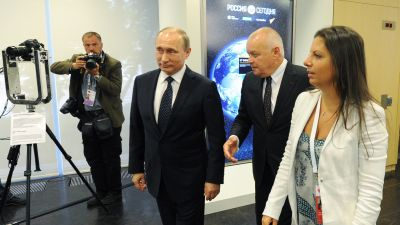 Russia's President Vladimir Putin, Rossiya Segodnya general director Dmitry Kiselev, Margarita Simonyan, editor-in-chief of Russia Today (RT) television news network and Rossiya Segodnya international news agency, (left to right) at the during a Putin visit to the international news agency's Moscow headquarters. (Photo by Mikhail KlimentyevTASS via Getty Images)