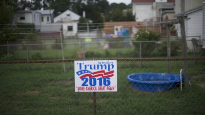 Trump sign on chainlink fence in front of backyard wading pool.