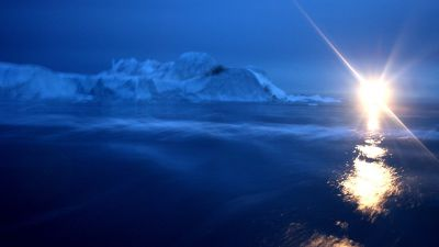 A boat lights the water surface as it passes by an iceberg in Jakobshavn Bay, Greenland. Scientists believe that Greenland, with its melting ice caps and disappearing glaciers, is an accurate thermometer of global warming. (Photo by Uriel Sinai/Getty Images)