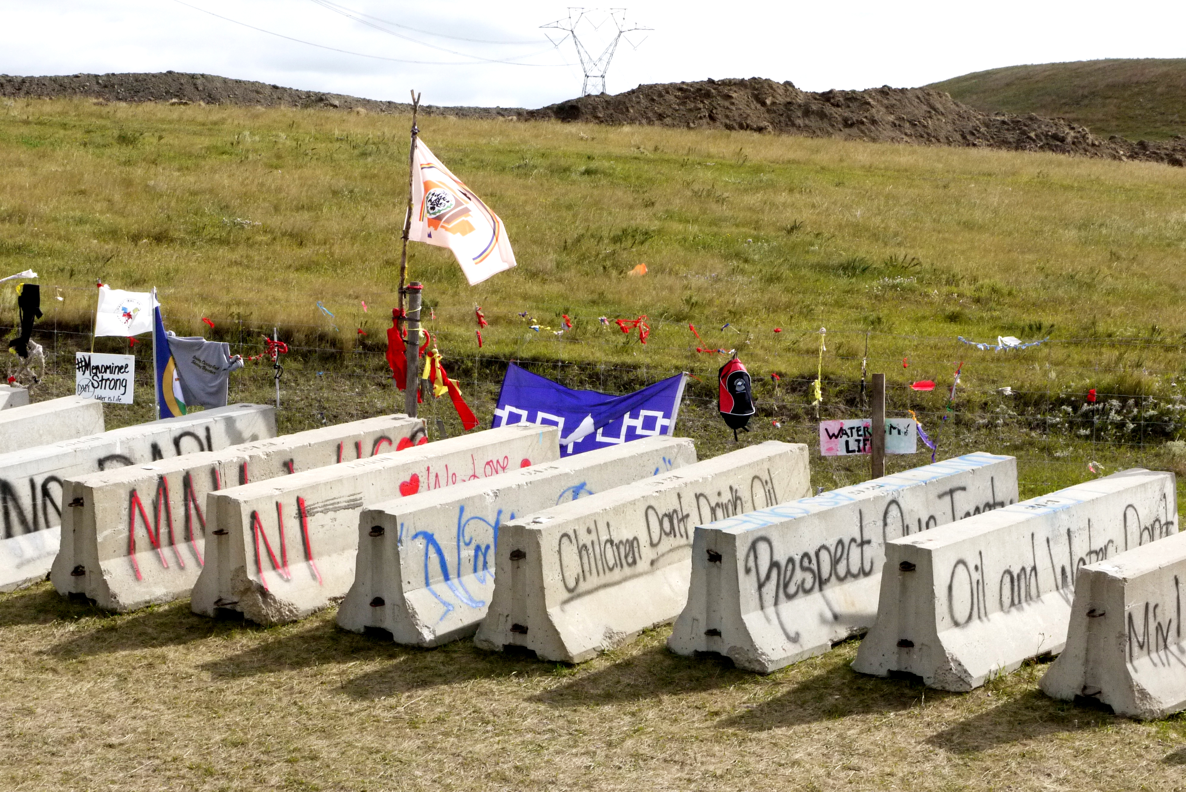"""Cement barriers painted with messages, such as """"Children Don't Drink Oil,"""" near the pipeline construction site, Sept. 13, 2016. (Sarah Jaffe for BillMoyers.com)"""