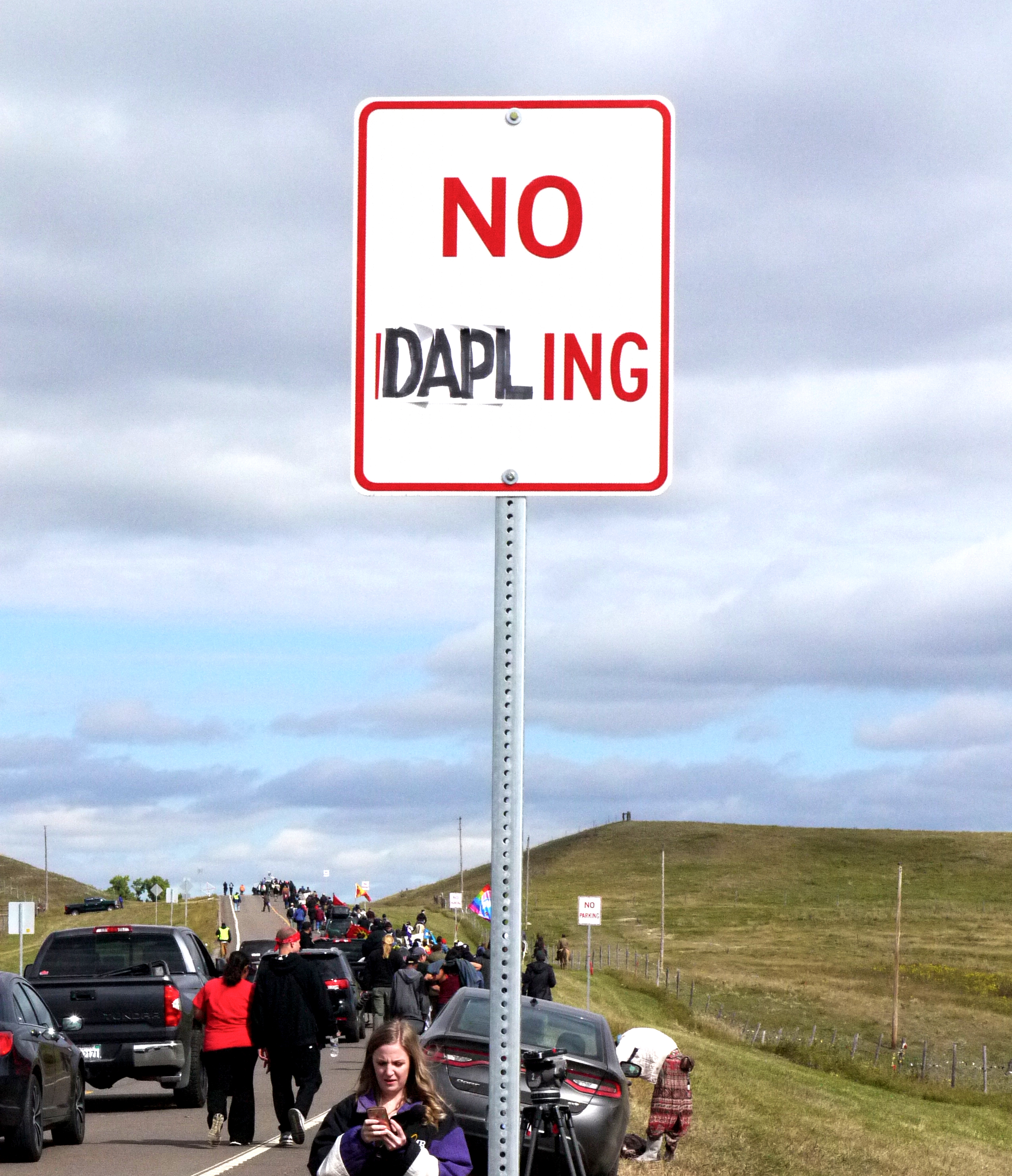 """An """"updated"""" road sign. Behind, people march from the Oceti Sakowin camp to the Dakota Access Pipeline construction site, Sept. 13, 2016. (Sarah Jaffe for BillMoyers.com)"""