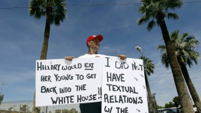 A demonstrator holds signs outside a Hillary Clinton rally in Arizona. (Photo by Ralph Freso/Getty Images)