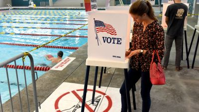 Woman at voting booth by swimming pool