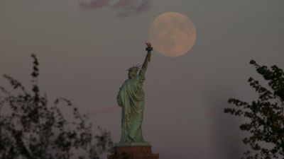 The moon rises behind the Statue of Liberty in New York City