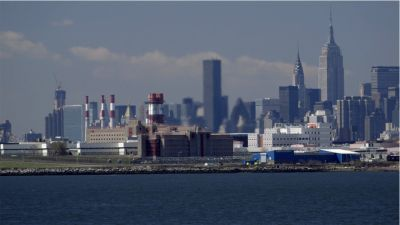A still from Rikers showing the buildings of Rikers jail and New York City in the background.