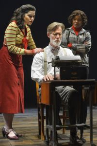 Two women flank fictional newspaper editor Doremus Jessup as he types an editorial.