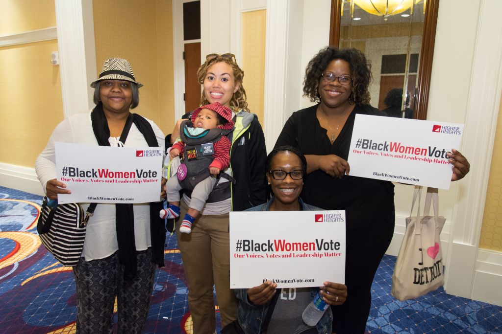 Women showing signs saying 'Black Women Vote' at the We Won't Wait Conference September 19-20, 2016.