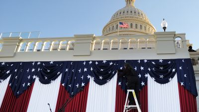 A worker adjusts flags on the US Capitol during preparations for the second inauguration of President Barack Obama on Jan. 18, 2013. (Photo by Jewel Samad/AFP/Getty Images)