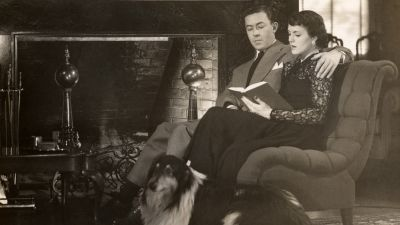 Couple sitting by fire and reading