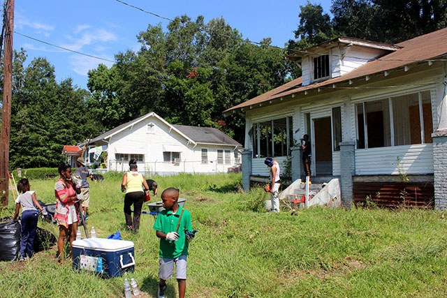 The Green Team Cooperative (focused on landscaping, composting and recycling) clean out a vacant house that was acquired by Cooperation Jackson for the development of its Community Land Trust. (Photo courtesy of Kali Akuno/Cooperation Jackson)