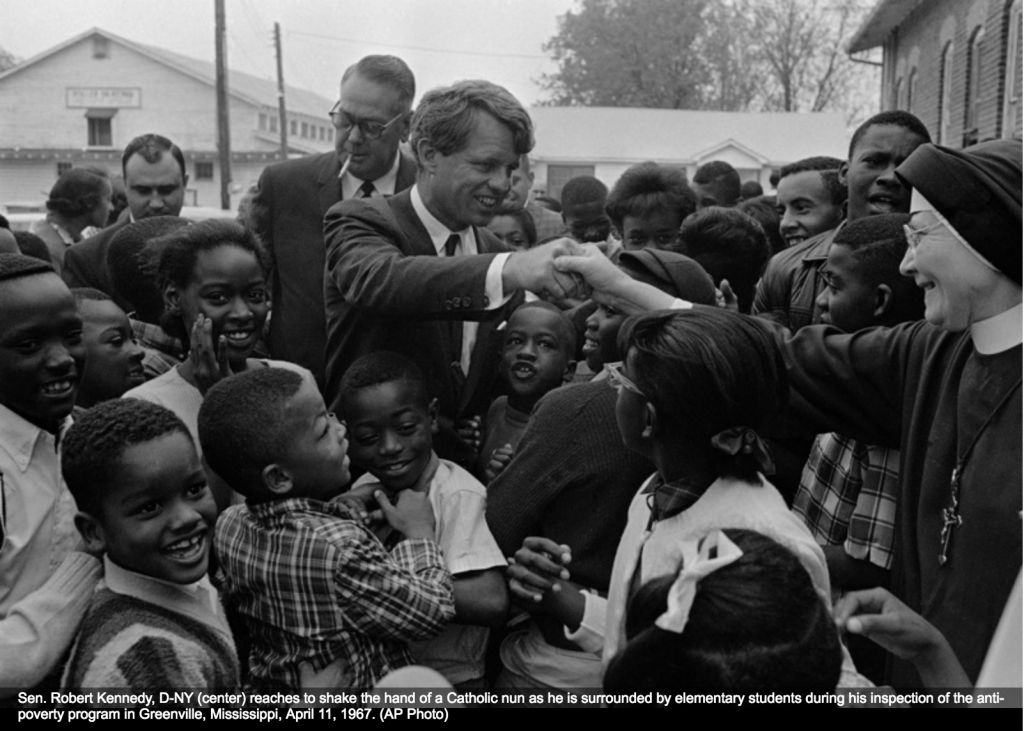 Sen. Robert Kennedy (D-NY) (center) reaches to shake the hand of a Catholic nun as he is surrounded by elementary school children during his inspection of an anti-poverty program in Greenville, Mississippi on April 11, 1967. (AP Photo)