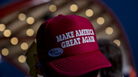 """An attendee wearing a hat reading """"Make America Great Again"""" waits for the arrival of Donald Trump during a campaign event in Cedar Rapids, Iowa, on Friday, Oct. 28, 2016. (Photographer: Daniel Acker/Bloomberg via Getty Images)"""