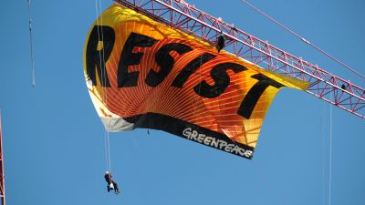 """Seven Greenpeace protesters scaled a construction crane blocks from the White House to hang this """"resist"""" banner. (Amaury Laporte/Flickr cc 2.0)"""