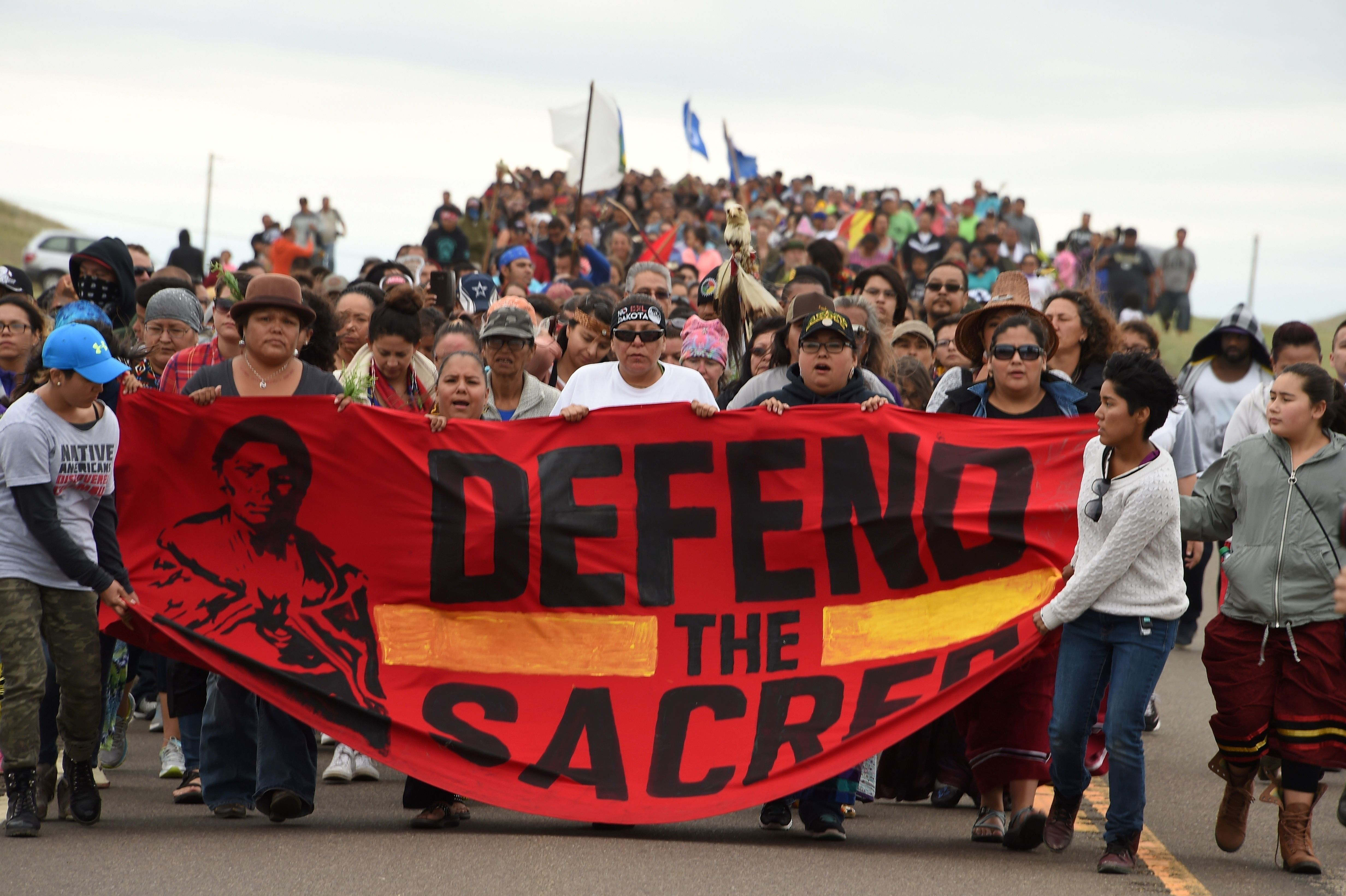 Native Americans march to the site of a sacred burial ground that was disturbed by bulldozers building the Dakota Access Pipeline (DAPL), near the encampment where hundreds of people have gathered to join the Standing Rock Sioux Tribe's protest of the oil pipeline slated to cross the nearby Missouri River, Sept. 4, 2016 near Cannon Ball, North Dakota. Protestors were attacked by dogs and sprayed with an eye and respiratory irritant yesterday when they arrived at the site to protest after learning of the bulldozing work. (Credit: Robyn Beck/AFP/Getty Images)